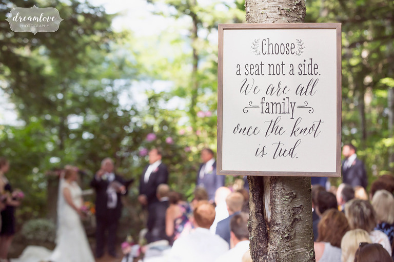 Lakeside wedding ceremony sign for guests to choose a seat.