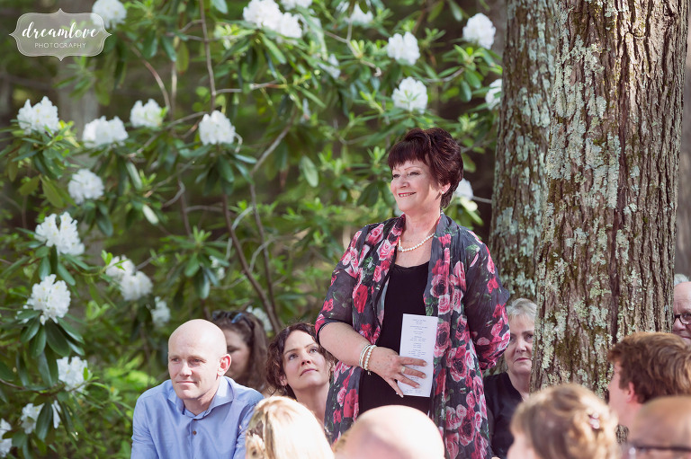 A wedding guests stands up during the quaker ceremony at the summer camp wedding in NH.