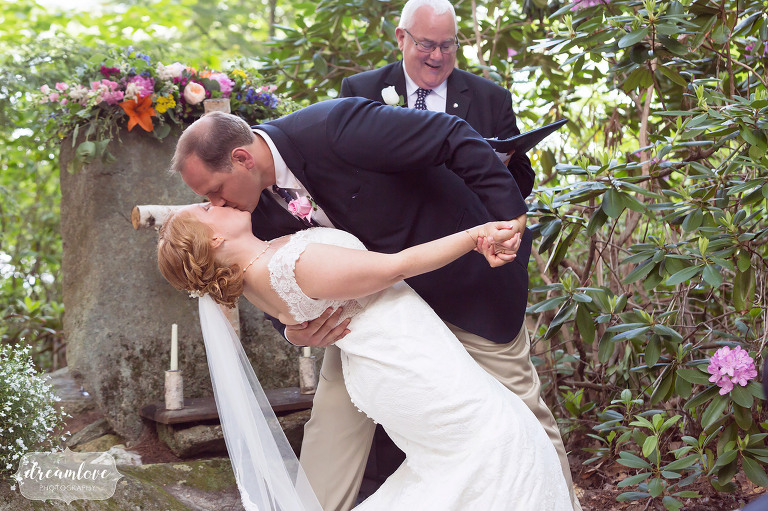 The groom dips his bride for their end of ceremony kiss at this outdoor summer camp wedding on Squam Lake.