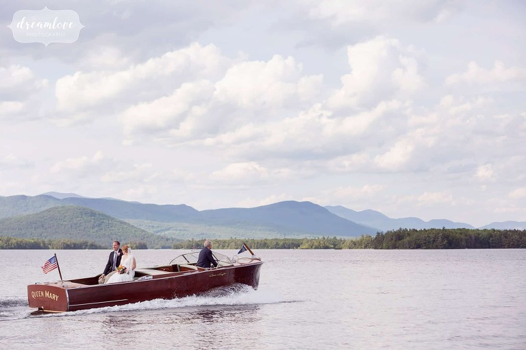 The bride and groom are rowed away in a wooden boat after their summer camp wedding on Squam Lake.