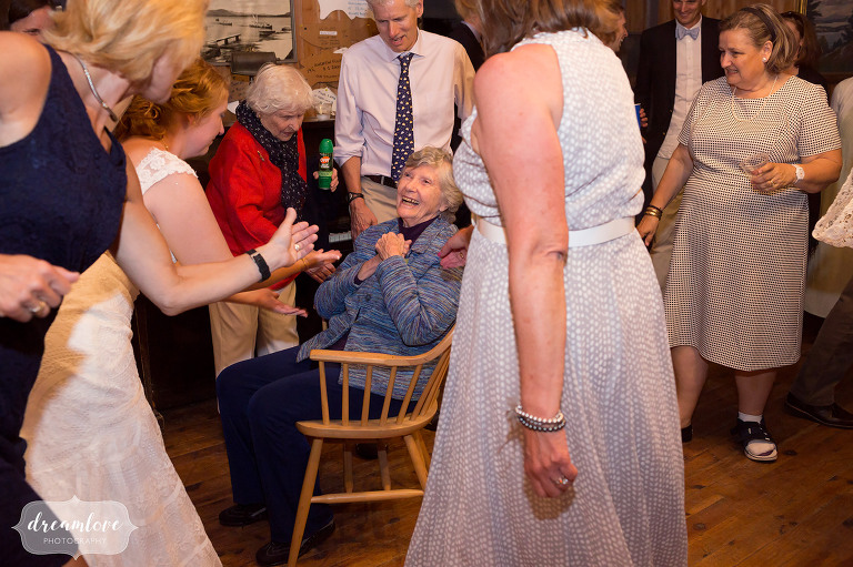Documentary photo of bride dancing with her grandmother at this summer camp wedding in NH.