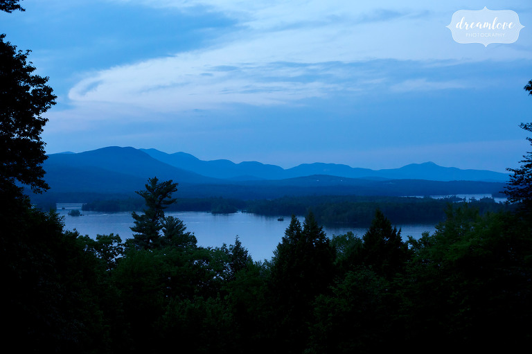 Beautiful twilight view of Squam Lake with mountains after a summer camp wedding here.