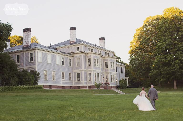 Wedding photography of the bride and groom walking back inside the Lyman Estate mansion in MA after their outdoor ceremony.