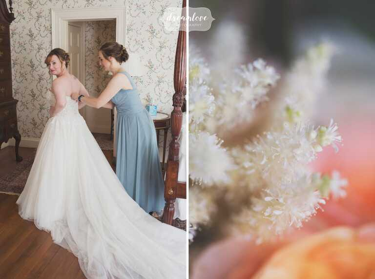 The bride puts her dress on with help from bridesmaids at the historic Lyman Estate wedding venue in MA.