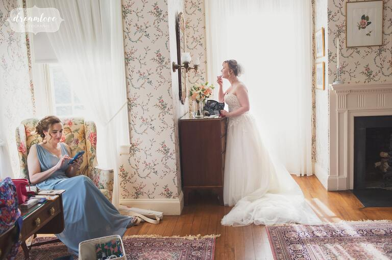 Photojournalistic style wedding photography coverage of the bride putting on make up at the Lyman Estate in MA.