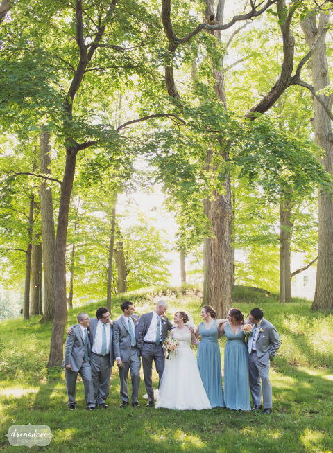Fairytale style photo of the wedding party under the trees at the historic Lyman Estate venue in Waltham.