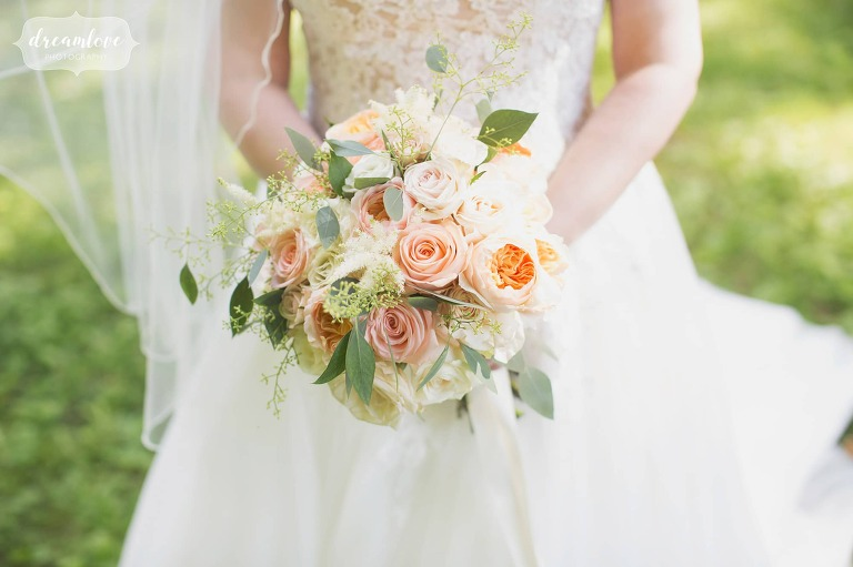 The bride holds a summer wedding bouquet of peach and green colors at the Lyman Estate.