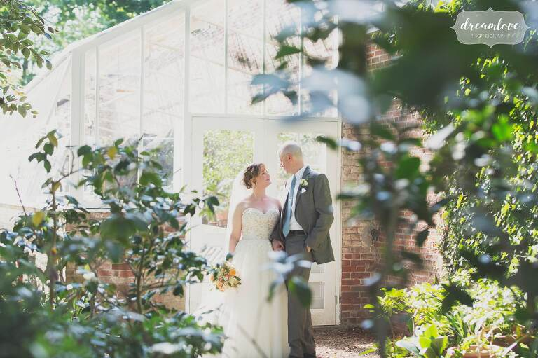 The bride and groom pose outside of the historic greenhouse at the Lyman Estate wedding venue in MA.