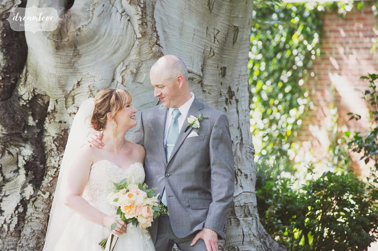 Natural wedding photography of the bride and groom outside next to the beech tree at the Lyman Estate greenhouse in MA.