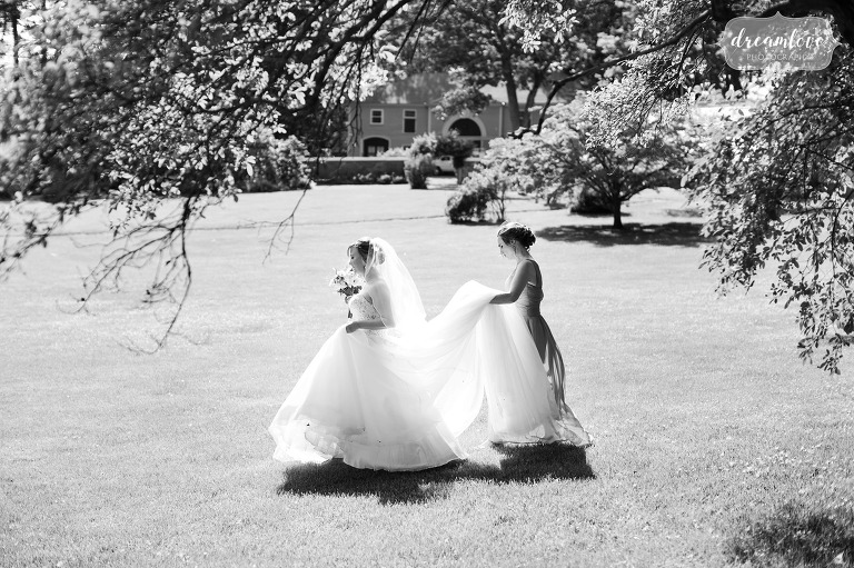The bride is helped by her bridesmaid walking across the field at the Lyman Estate in MA.