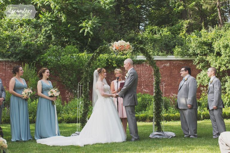 English garden outdoor wedding ceremony with a floral arbor with ivy at the Lyman Estate.