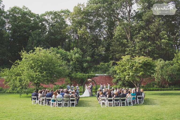 A garden wedding ceremony outdoors at the historic Lyman Estate venue in Waltham, MA.