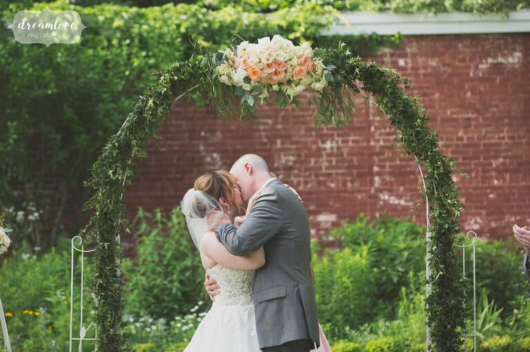 The bride and groom kiss under a ceremony arch of flowers at the Lyman Estate.