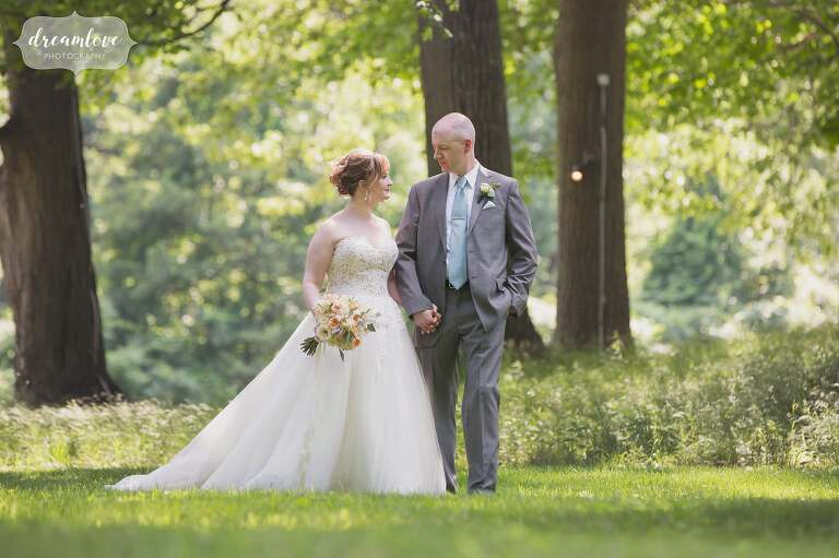 The bride and groom walk through the woods at the Lyman Estate in MA.