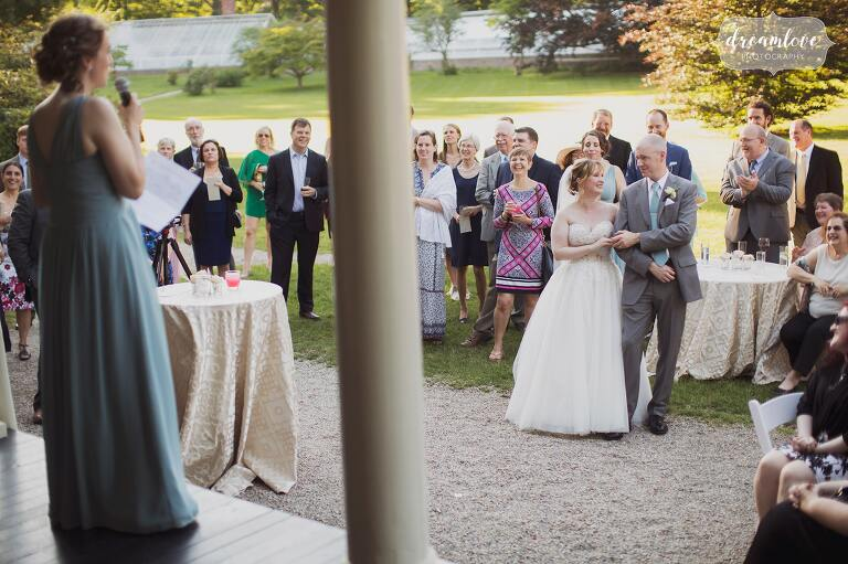 The maid of honor gives a speech on the wrap around porch at the historic Lyman Estate venue in MA.