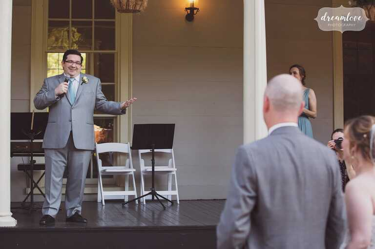 The best man gives a funny speech on the porch at the Lyman Estate in MA.