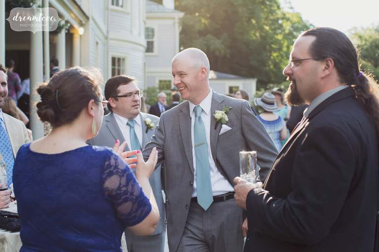 The groom mingles with wedding guests during the cocktail hour at the Lyman Estate in MA.