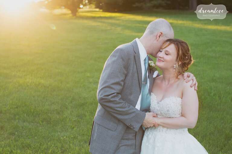 The bride and groom embrace in a sunbursty field at the Lyman Estate.