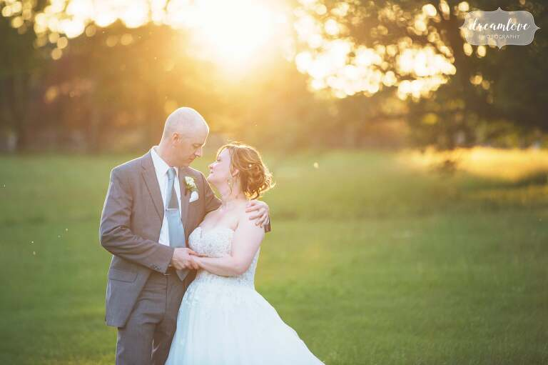 Bride and groom stand in the sunset light outside of the Lyman Estate wedding venue near Boston, MA.