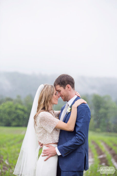 Lisa Mara, the bride, and groom Tyson Bry embrace in the rain on the Stowe Quiet Path in VT before their barn wedding.