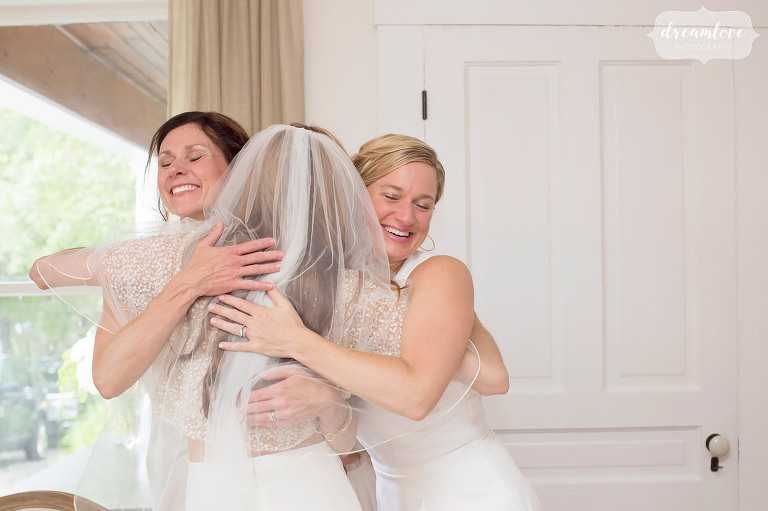 The bride is hugged by her two sisters and maids of honor after giving gifts before her barn wedding in Stowe.