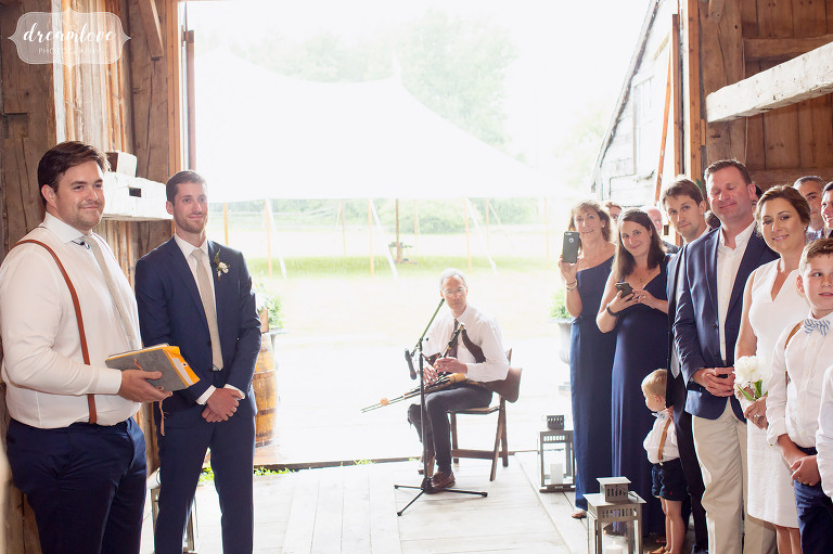 The groom watches his bride enter the ceremony at the Comfort Farm barn in Stowe on a rainy day.