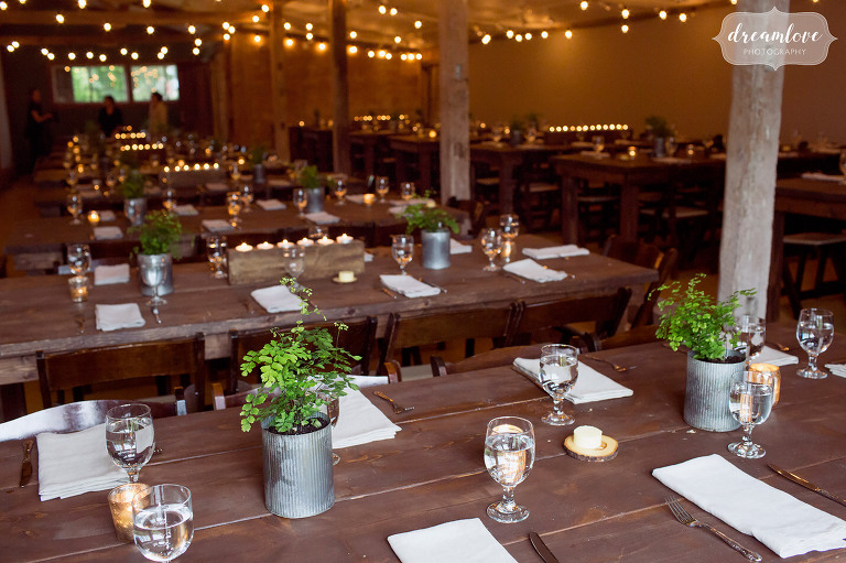 A farmhouse style wedding reception dinner is set up in the Comfort Farm in Stowe. We loved the galvanized planters with live plants as centerpieces at this rustic wedding.