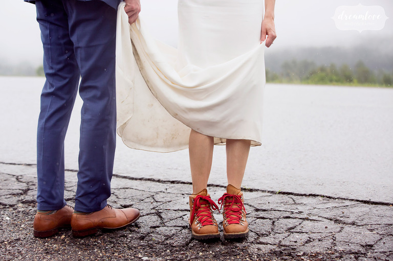 Love this rainy wedding detail photo of the bride and groom's feet while standing on wet pavement in Stowe, VT. The bride wore Danner hiking boots with red laces to keep her feet dry!