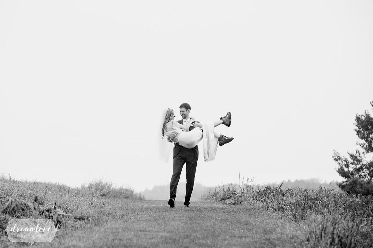 Documentary wedding photography of the groom carrying the bride down the Stowe Quiet Path on a rainy day.