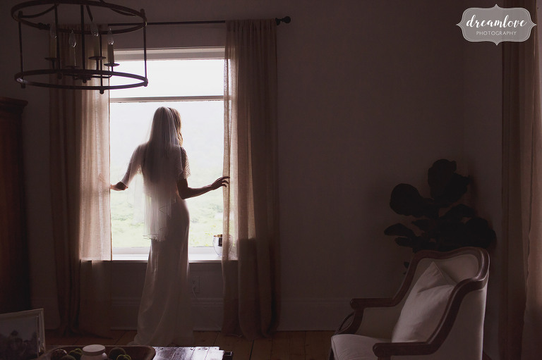 A fine art wedding photo of the bride looking out her window at the rain in Stowe, VT after her barn wedding ceremony.