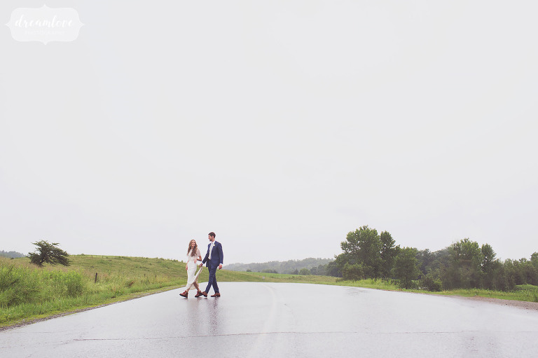 The bride and groom walk across a wet road on the way to the Stowe Quiet Path in VT.