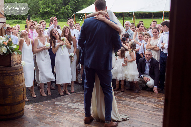 Guests react to a funny first dance move by the bride at this Stowe, VT barn wedding reception.