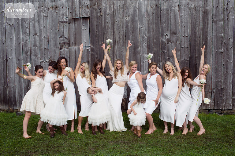 The bridesmaids acting crazy with gray barn in the background at this Stowe, VT wedding.