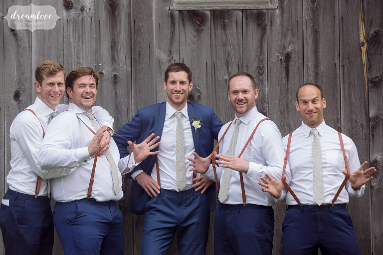 A funny photo of the groomsmen while pulling at their suspenders at this barn wedding in Stowe.
