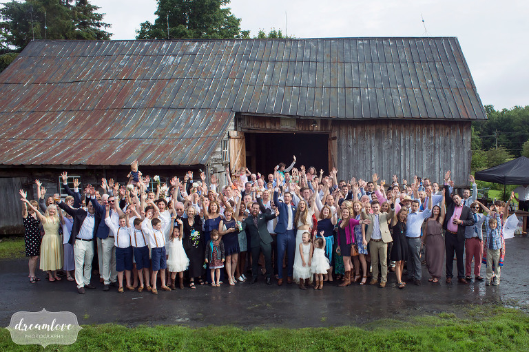 A photo of all of the wedding guests outside of the Comfort Farm barn for a rainy wedding in Stowe.