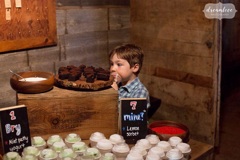 Best documentary wedding photo of a little boy looking at the wedding cake desserts when no one else is watching in Stowe, VT.