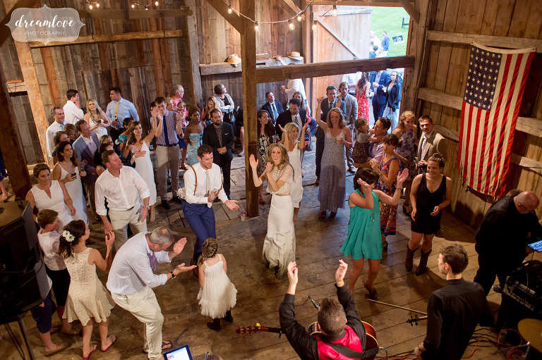 Photo of the bride and groom dancing on the barn floor while surrounded by wedding guests as the McLean Ave band performs at this Stowe reception.