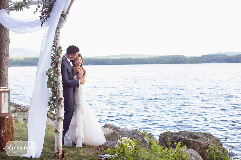 Bride and groom stand on the shore of Lake Wentworth after their Wolfeboro NH wedding.