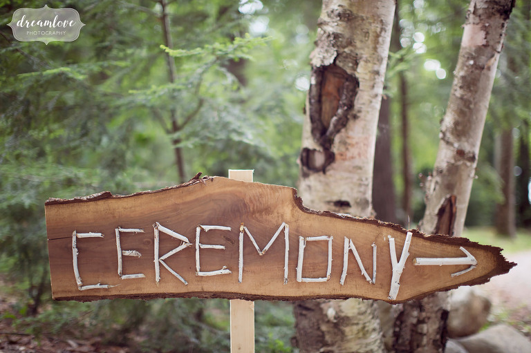 A handmade wooden sign with birch twigs tells guests where the outdoor ceremony will be on the lake in Wolfeboro, NH.