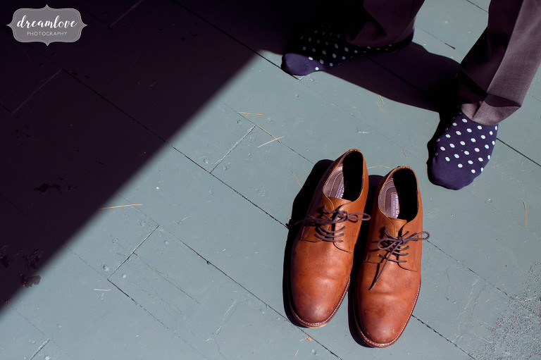 Fine art wedding photo of the groom wearing polka dot navy socks and Allen Edmonds shoes at this outdoor wedding near Lake Winnipesaukee in NH.