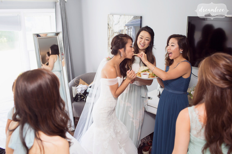 Funny documentary wedding photo of the bridesmaids feeding the bride french fries before the wedding in Wolfeboro, NH.