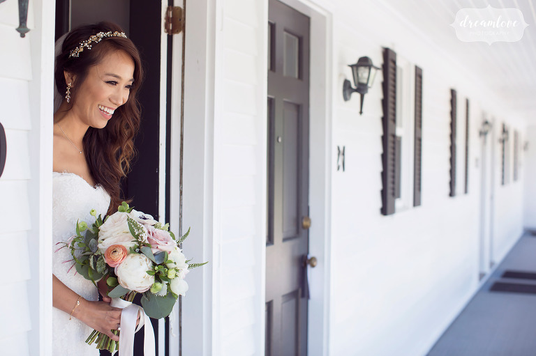 The bride stands on the porch at the Inn on Main before her Wolfeboro lakes region wedding.