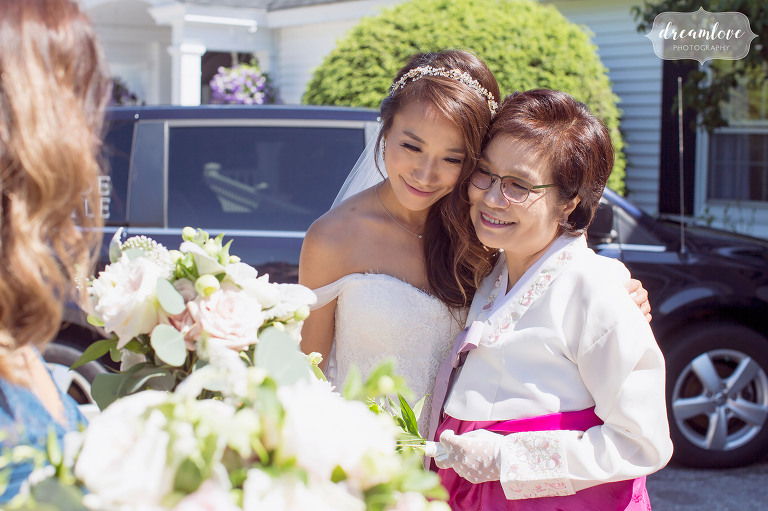 The bride hugs her mother, who is wearing a traditional Korean outfit for the wedding in NH.