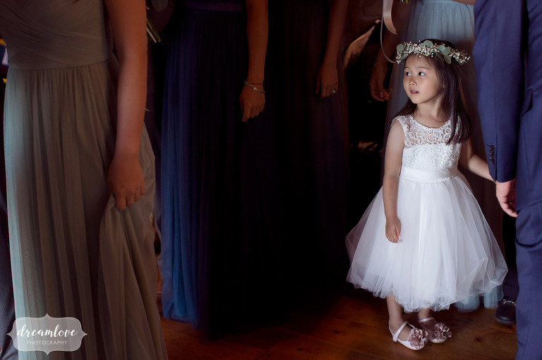 Candid wedding photography of the flower girl waiting for her turn to walk down the aisle at this outdoor wedding in Wolfeboro.