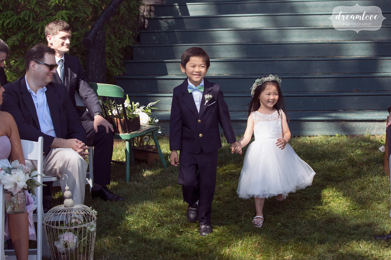 Documentary wedding photo of the ring bearer and flower girl walking down aisle at this Korean wedding in NH.