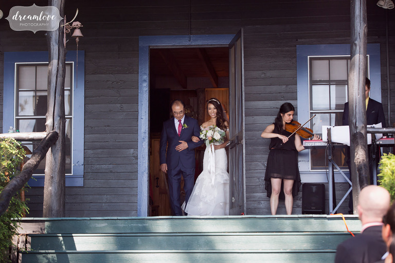 The bride and her father walk from their house for this outdoor summer wedding on the lake in Wolfeboro, NH.