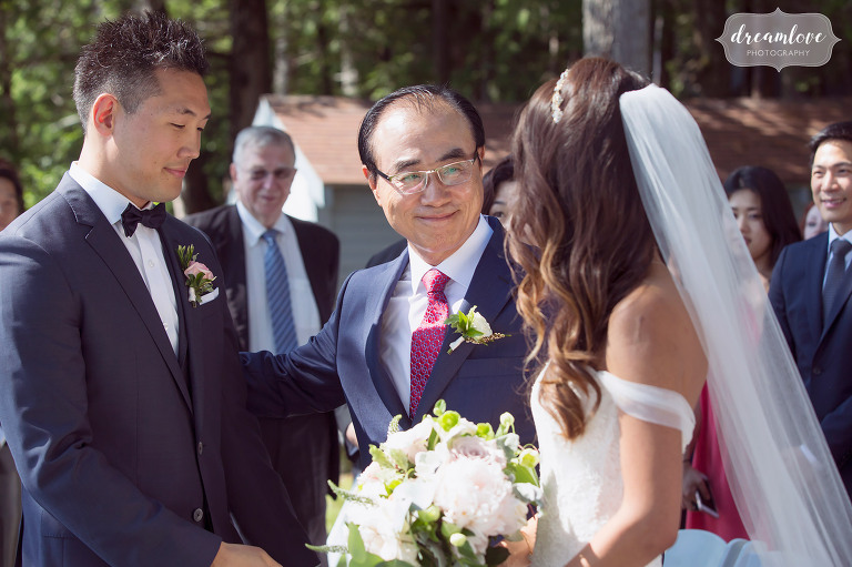 The father of the bride gives his daughter away at this Korean wedding ceremony on the lake in Wolfeboro, NH.