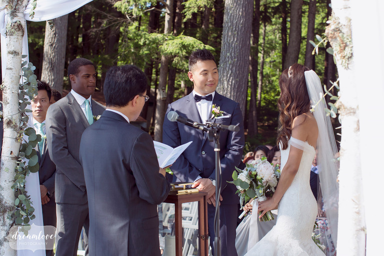 The groom smiles at the bride during this lakeside wedding in Wolfeboro.