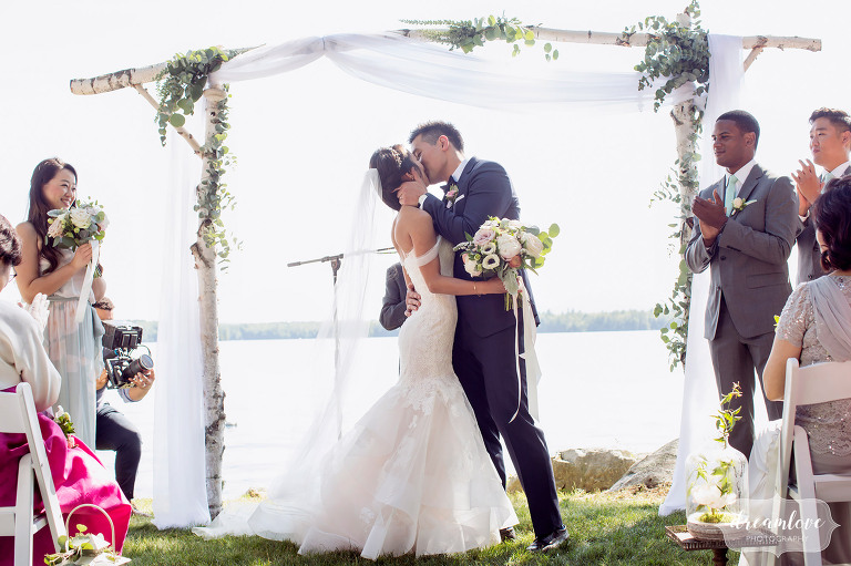 The bride and groom have the ceremony kiss in this natural wedding photo.