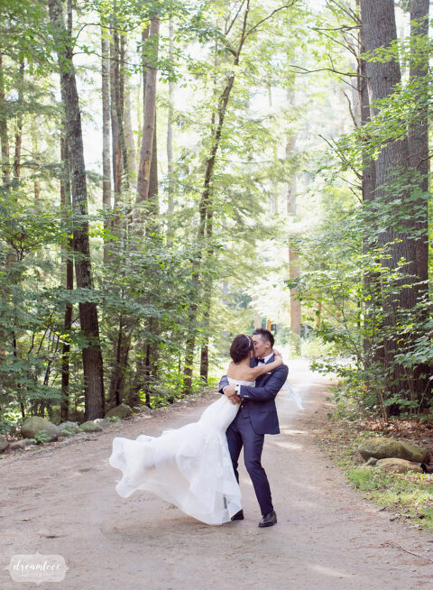 This woodland wedding photo of the bride and groom swinging around under the trees in Wolfeboro, NH is magical.